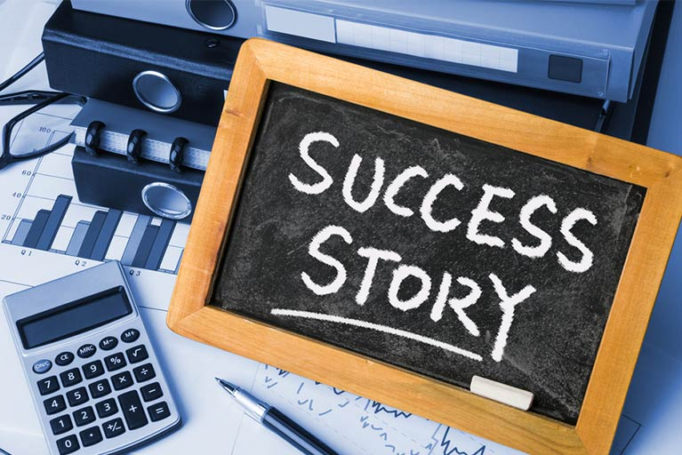 success story written on a blackboard on a desk with calculator